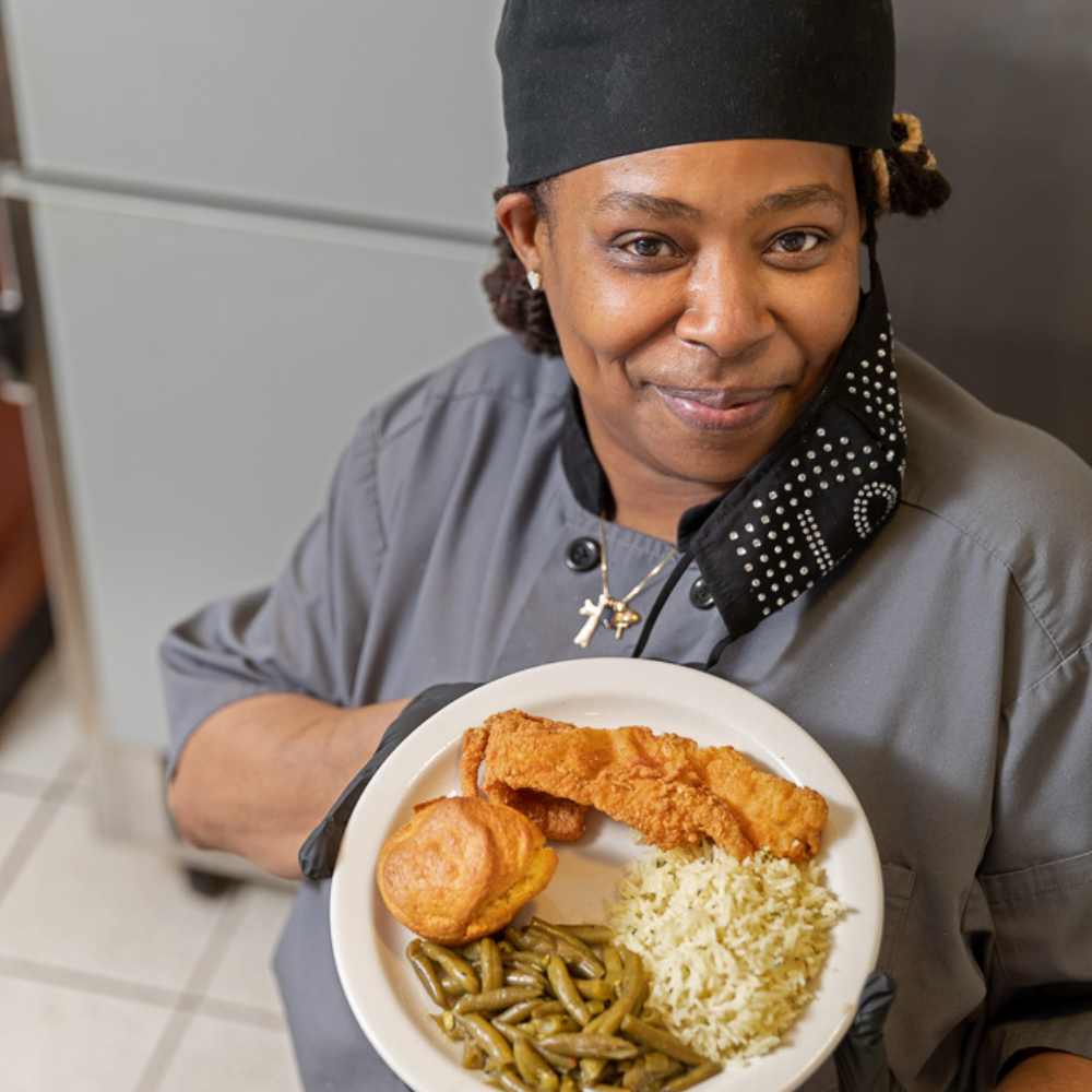 Burnell Gilliam dressed in her chef attire offers a plate of food at her food station.