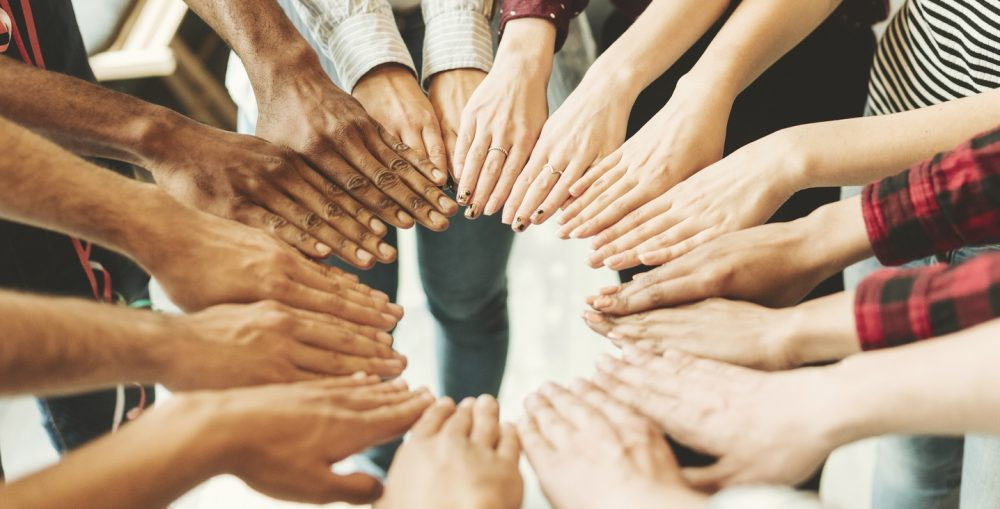 Group of people with hands together in a circle