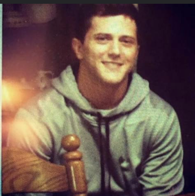 Hayden Miller dressed in a gray hoodie and smiling.