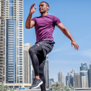 Man in purple athletic top and gray leggings exercise with an urban backdrop.