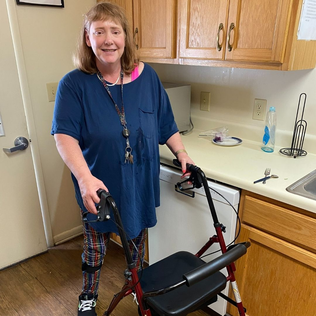 Windermere resident Stephanie Williams using her rolling walker wearing a blue top and printed pants in the home's kitchen.