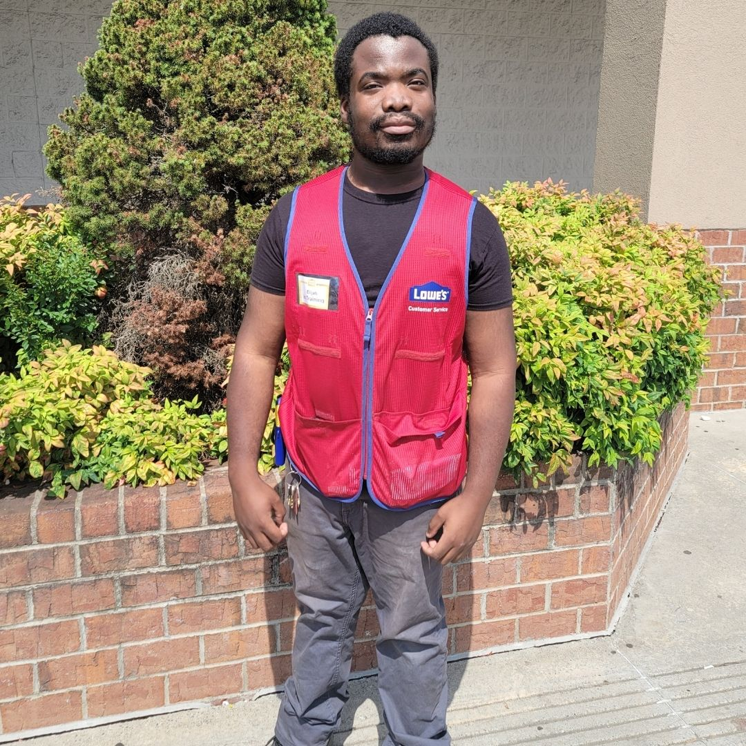 Elijah White stands in his work uniform of red vest with gray pants and black short sleeved shirt.