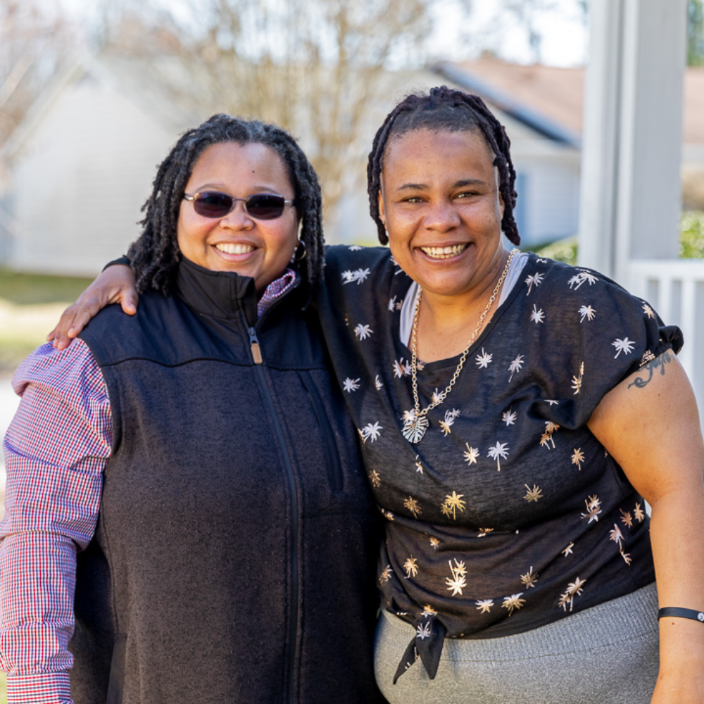 DSP Joanna Watson, left, and Kristina Smith, right, pose outside her new home.