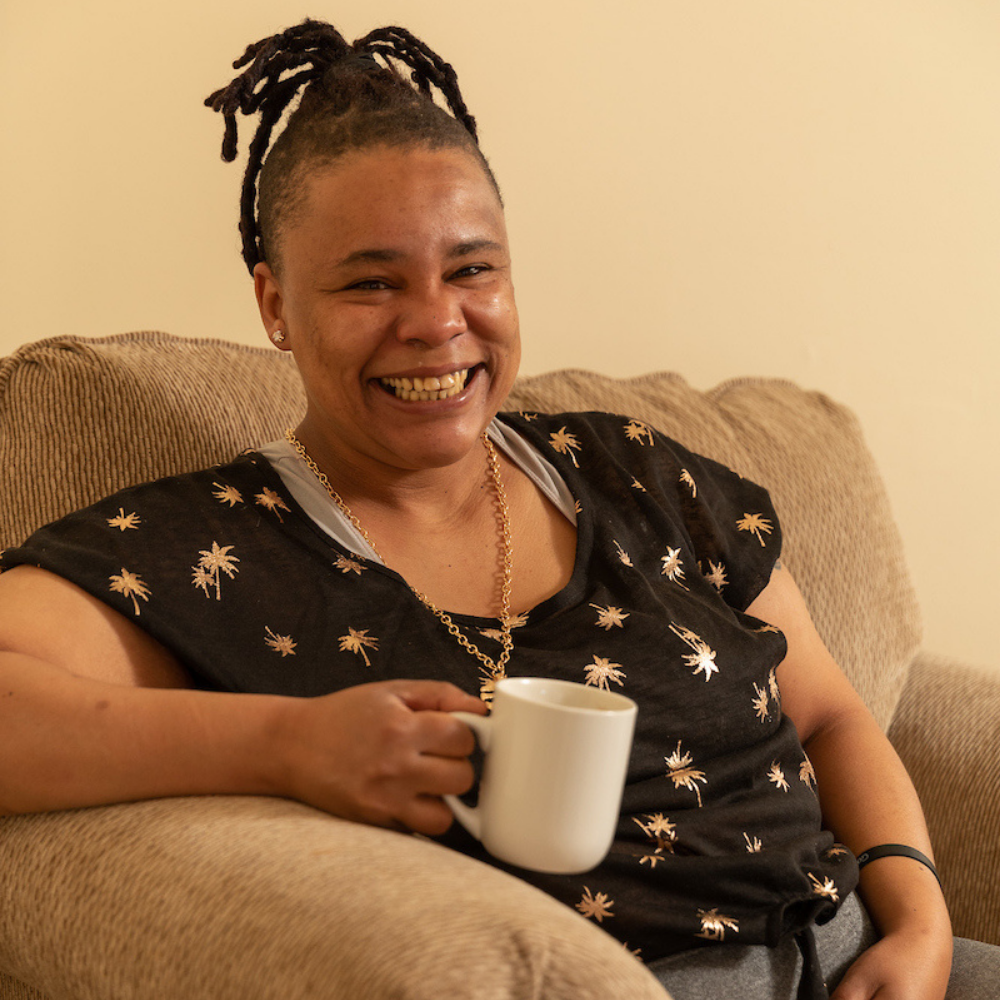 Monarch supported person Kristina Smith dressed in a black flowered shirt and holding a white coffee mug.