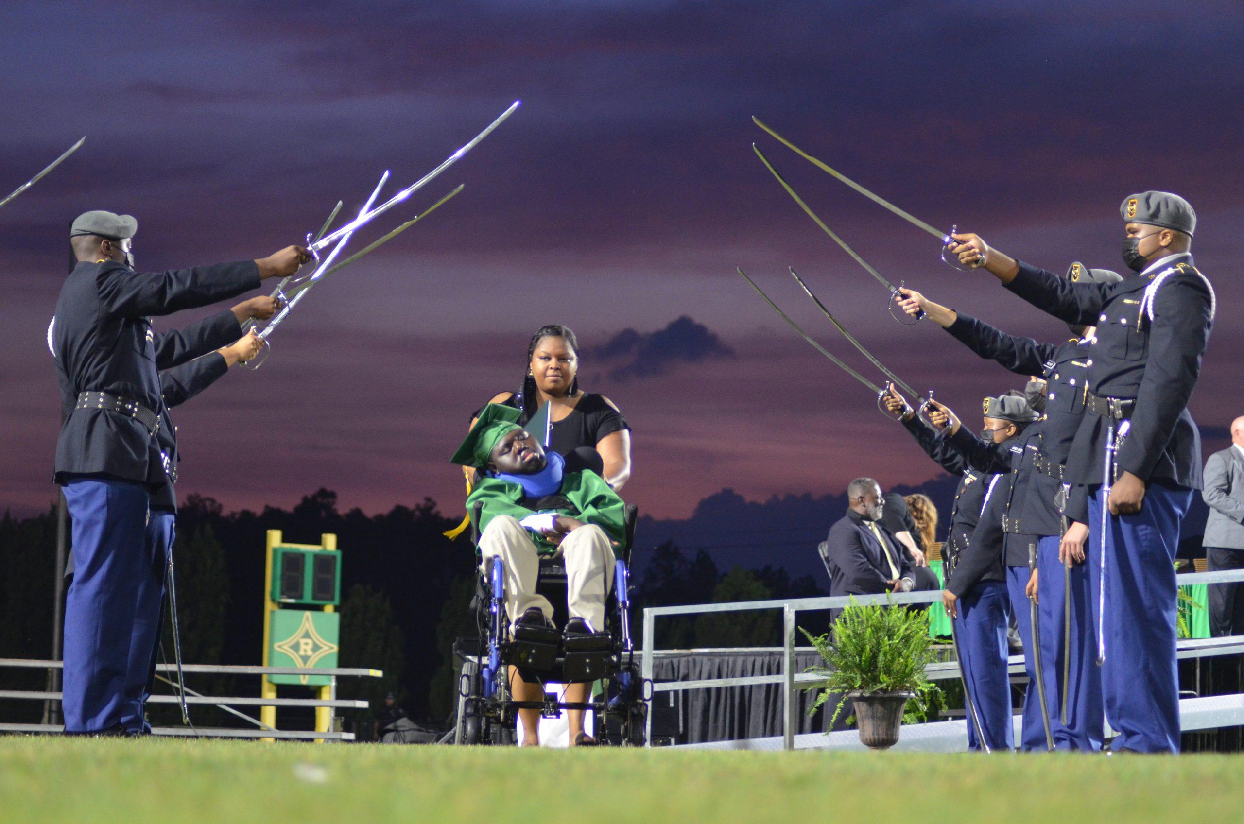 Timothy Bethea, dressed in green cap and gown, is accompanied by teacher Takia York at Richmond Senior High School's Raider Stadium.