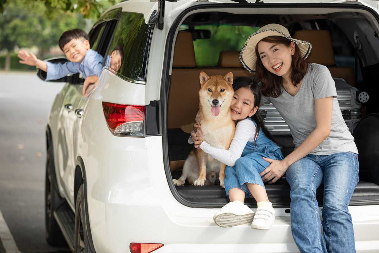 Children and mom preparing to leave for a summer trip in white car.