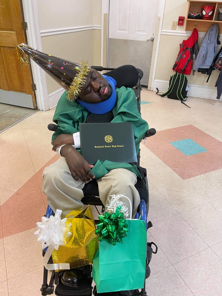 Pence Place resident Timothy Bethea wearing his green high school graduation cap and gown holding his diploma.