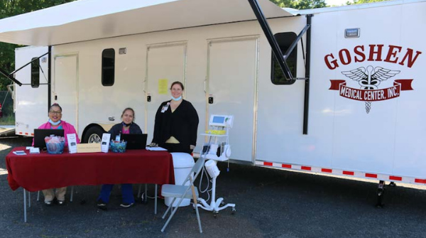 From left, Dionne Robinson, MA, site leader at the Hamlet, Rockingham and Albemarle Goshen locations, Tara Clark, MA, Goshen medical assistant, and Nurse Practitioner Sheila Brown, DNP, AGNP-C, pose in front of the Goshen Medical Center mobile unit in Albemarle during a recent health fair at Monarch.