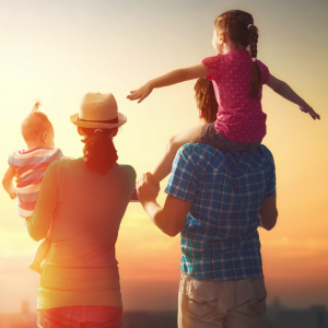 Mother, father and two children watching a sunset.