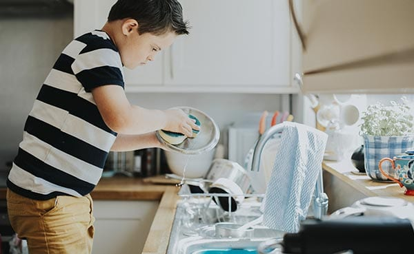 Boy learning life lessons and washing dishes